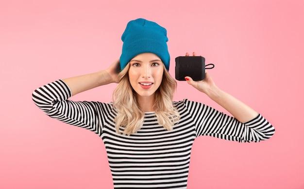 Jeune jolie femme tenant haut-parleur sans fil écouter de la musique portant une chemise rayée et un chapeau bleu souriant heureux humeur positive posant sur fond rose isolé