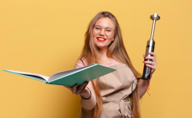 Jeune jolie femme tenant un livre de recettes et un mélangeur