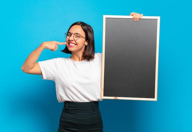 Jeune jolie femme tenant un tableau noir