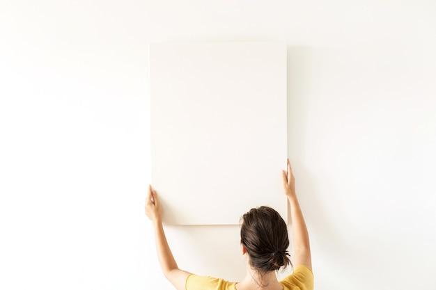 Jeune jolie femme tenir une toile vierge avec espace de copie de maquette vide