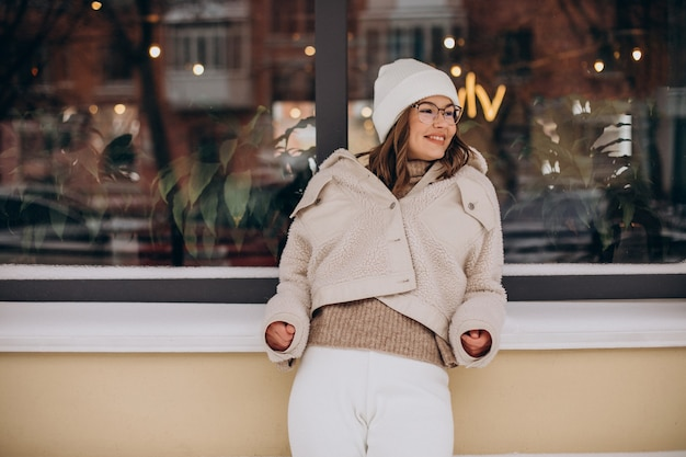 Jeune jolie femme en tenue beige marchant dans la rue à l'heure d'hiver