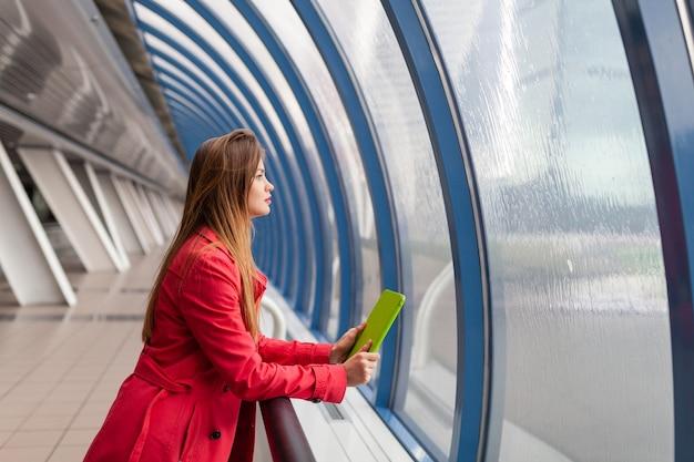 Jeune jolie femme en tenue décontractée tenant un ordinateur portable tablette dans un bâtiment urbain