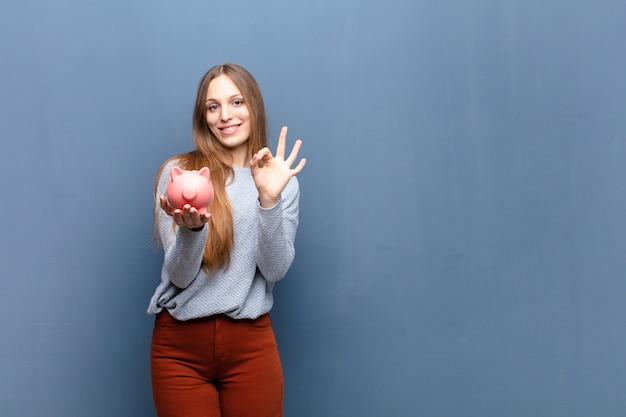 Jeune jolie femme avec une tirelire contre le mur bleu avec une surface