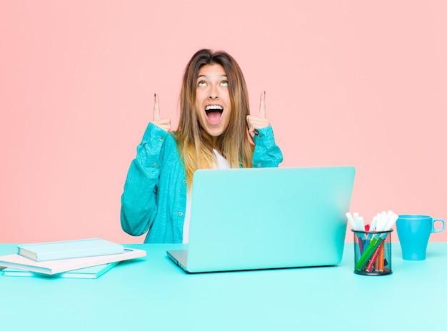 Jeune jolie femme travaillant avec un ordinateur portable, l'air choqué, étonné et bouche bée, pointant vers le haut avec les deux mains pour copier l'espace