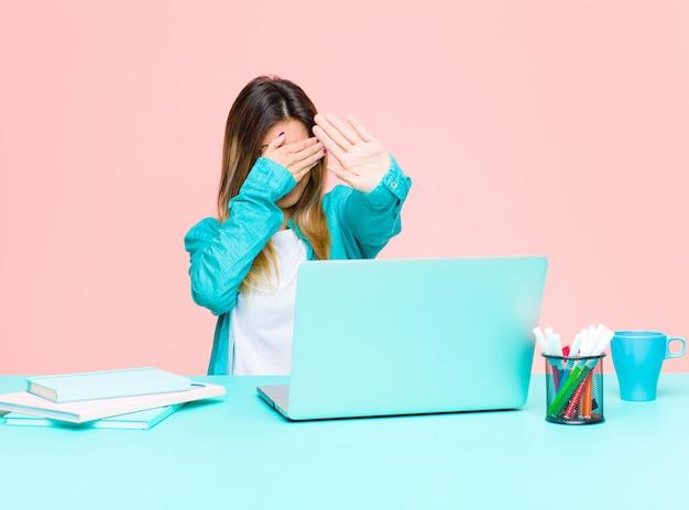 Jeune jolie femme travaillant avec un ordinateur portable couvrant le visage