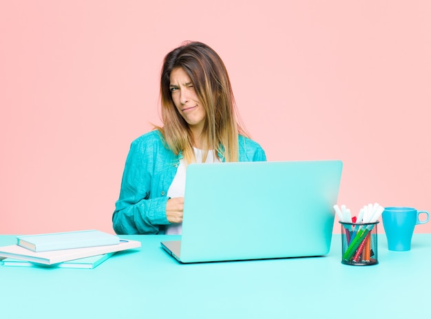 Jeune jolie femme travaillant avec un ordinateur portable, heureuse et amicale, souriante et qui vous jette un œil sur vous avec une attitude positive