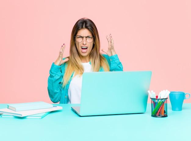 Jeune jolie femme travaillant avec un ordinateur portable hurlant avec les mains en l'air se sentant furieux frustré stressé et contrarié