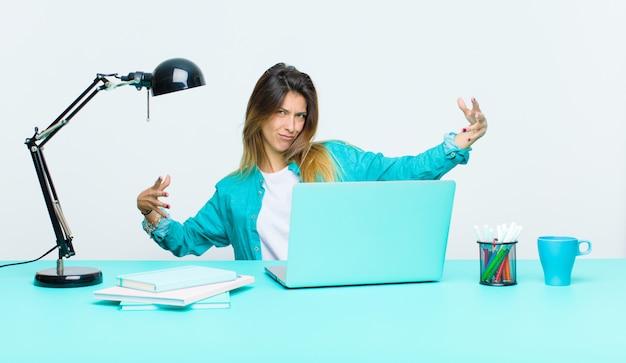 Jeune jolie femme travaillant avec un ordinateur portable, semblant heureuse, arrogante, fière et satisfaite de soi, se sentir comme une numéro un