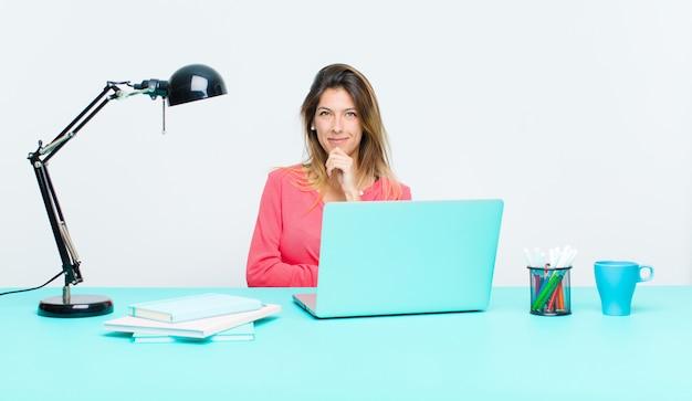 Jeune jolie femme travaillant avec un ordinateur portable, semblant heureuse et souriante, la main sur le menton, se demandant ou posant une question, comparant les options