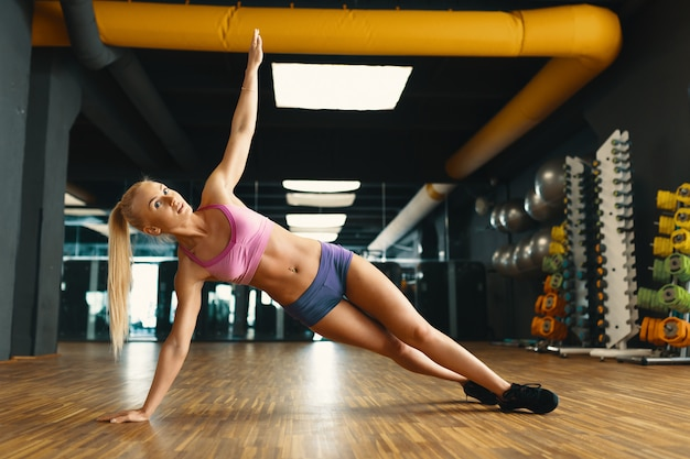 Jeune jolie femme travaillant avec un poids personnel dans une salle de sport moderne