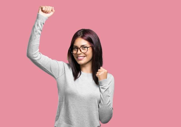 Jeune jolie femme très heureuse et excitée levant les bras célébrant une victoire ou un succès