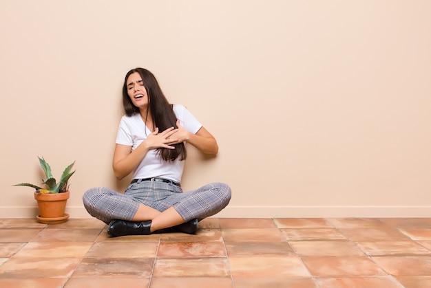 Jeune jolie femme à la triste, blessée et le cœur brisé, tenant les deux mains près du cœur, pleurant et se sentant déprimé assis sur un sol