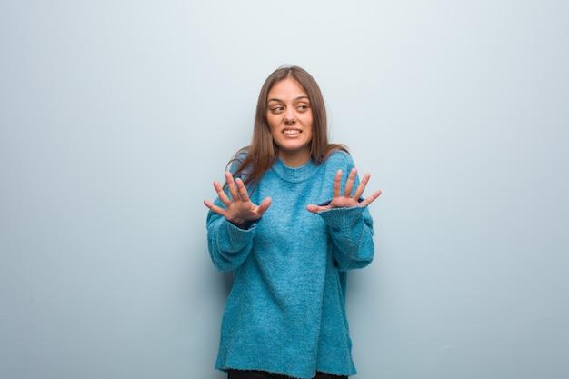 Jeune jolie femme vêtue d'un pull bleu rejetant quelque chose faisant un geste de dégoût