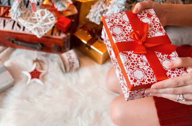 Une jeune jolie femme vêtue de vêtements chauds et confortables est assise par terre dans sa maison lumineuse près de l'arbre de noël et tient une boîte-cadeau dans ses mains.