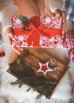 Une jeune jolie femme vêtue de vêtements chauds et confortables est assise sur le parquet clair dans sa maison lumineuse près de l'arbre de noël et tient une boîte-cadeau dans ses mains.