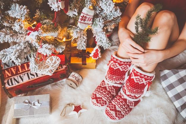 Une jeune jolie femme vêtue de vêtements chauds et confortables est assise sur le parquet clair dans sa maison lumineuse près du sapin de noël et tient une branche de sapin dans ses mains.