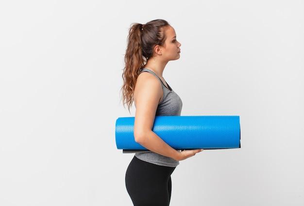 Jeune jolie femme en vue de profil pensant, imaginant ou rêvant et tenant un tapis de yoga