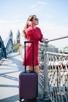 Jeune jolie fille admirant la beauté de la ville depuis le pont. voyageuse vient d'arriver dans une nouvelle ville et désireuse de l'explorer