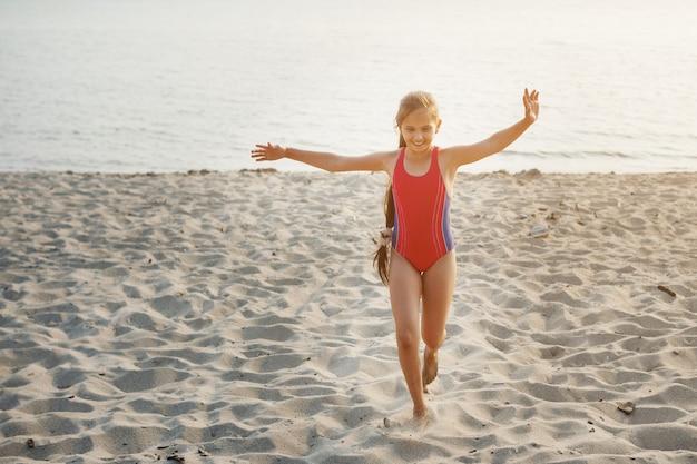 Jeune jolie fille adolescente en maillot de bain rouge longe une plage de sable au bord de la mer.