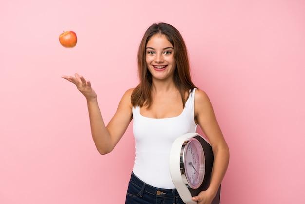 Jeune jolie fille avec appareil de pesage et avec un fond de pomme