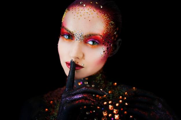 Jeune jolie fille en art lumineux-maquillage, peinture corporelle. toucher les lèvres