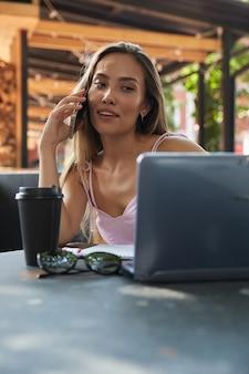 Jeune jolie fille asiatique appelant par smartphone buvant du café au café d'été