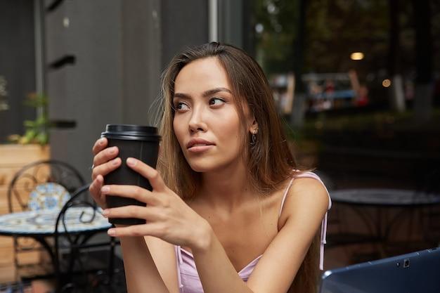 Jeune jolie fille asiatique assise à l'extérieur du café avec un ordinateur portable buvant du café