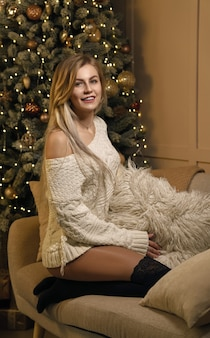 Jeune jolie fille assise sur un canapé et arbre de noël décoré