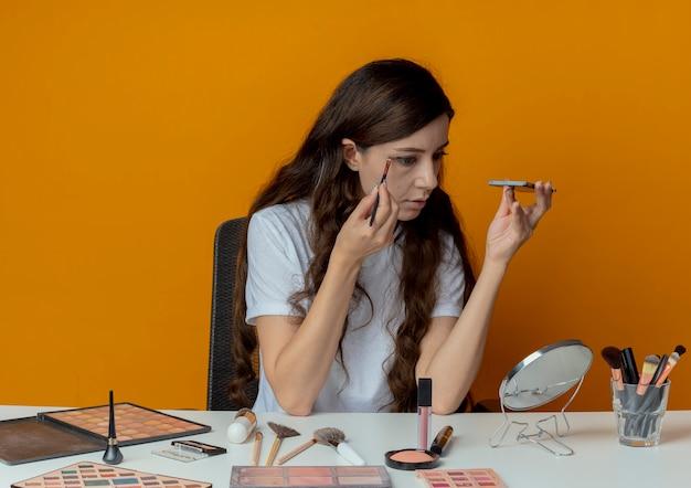 Jeune jolie fille assise à la table de maquillage avec des outils de maquillage regardant un miroir et appliquant un fard à paupières