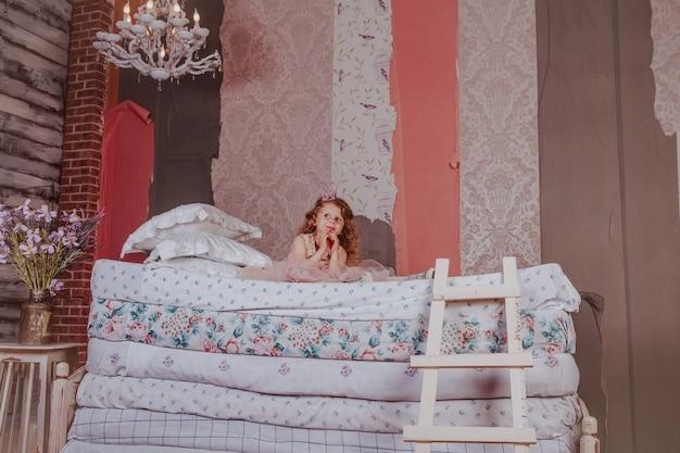 Jeune jolie fille assise sur un tas de matelas