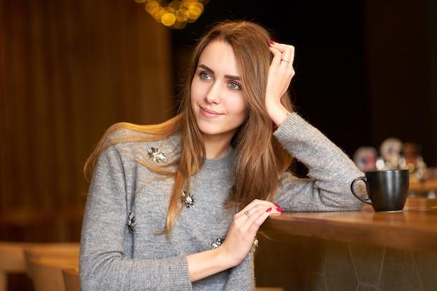 Jeune jolie fille aux cheveux longs, boire du café ou du thé dans le café.