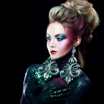 Jeune jolie fille blonde en art lumineux-maquillage, cheveux hauts, peinture corporelle. strass et paillettes