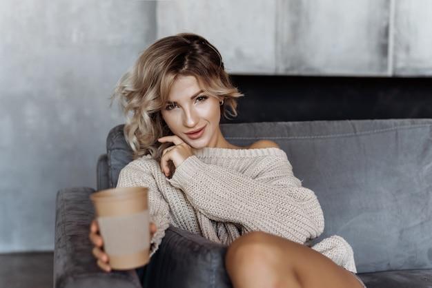 Jeune jolie fille blonde assise sur un canapé