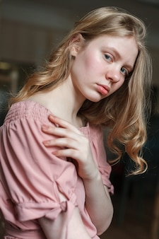 Jeune jolie fille blonde aux yeux bleus en robe rose, inclinant la tête.