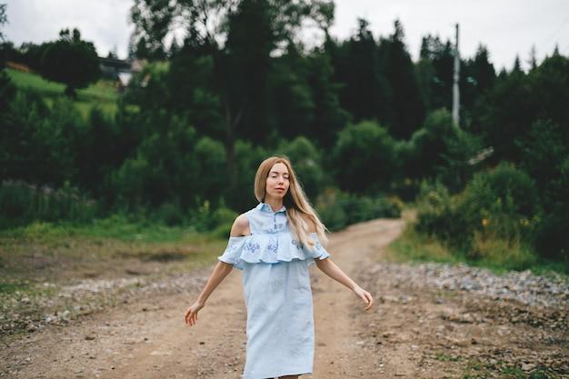 Jeune jolie fille blonde élégante en robe bleue posant sur la route à la campagne
