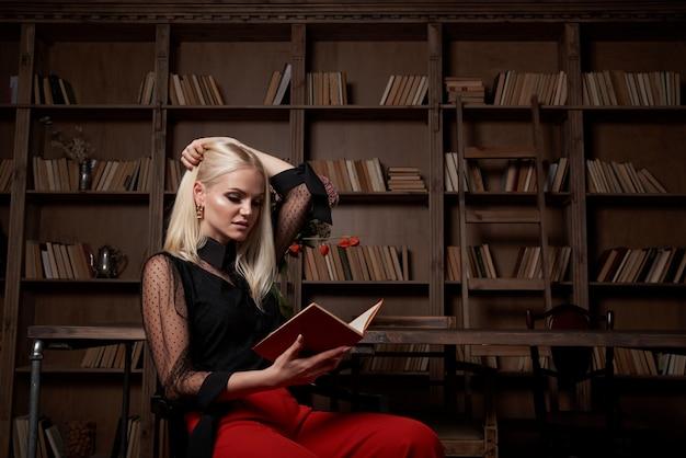 Jeune et jolie fille blonde lit un livre à la bibliothèque