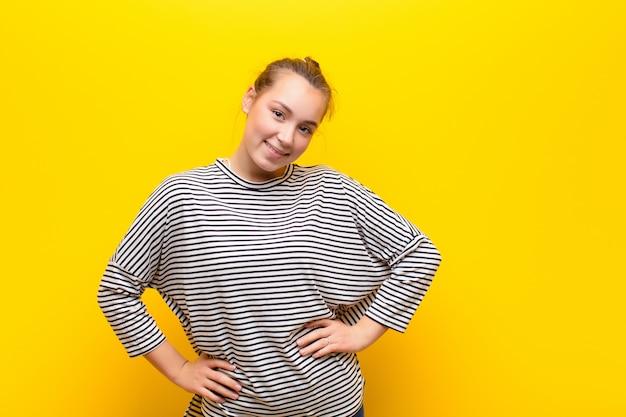 Jeune jolie fille blonde à la recherche de plaisir, de bonne humeur et confiant, souriant fièrement et à côté avec les deux mains sur les hanches contre le mur jaune