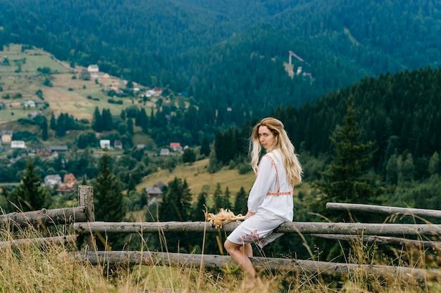 Jeune jolie fille blonde en robe blanche avec ornement assis sur une clôture en bois avec bouquet d'épillets sur un paysage de campagne pittoresque