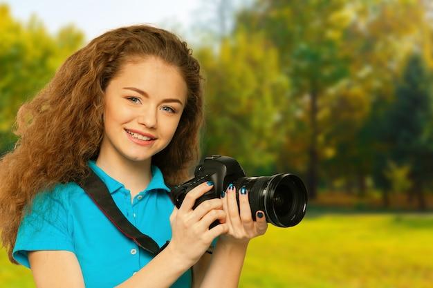 Jeune jolie fille avec caméra dans parc automne