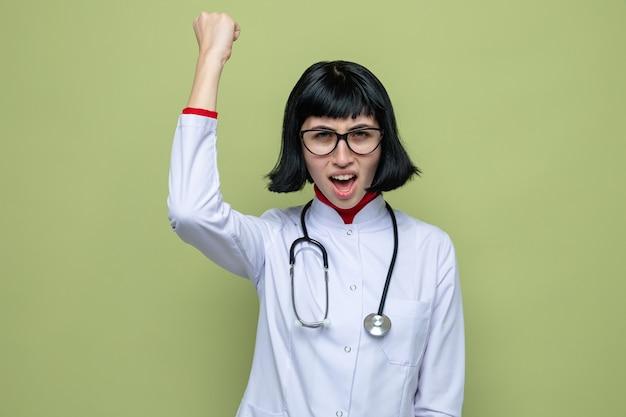 Jeune jolie fille caucasienne agacée avec des lunettes optiques en uniforme de médecin avec stéthoscope levant le poing