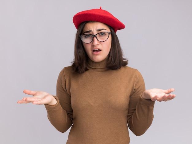 Jeune jolie fille caucasienne ignorante avec un chapeau de béret et dans des lunettes optiques, tenant les mains ouvertes et regardant la caméra
