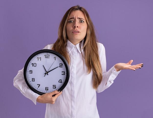 Une jeune jolie fille caucasienne ignorante garde la main ouverte et tient l'horloge