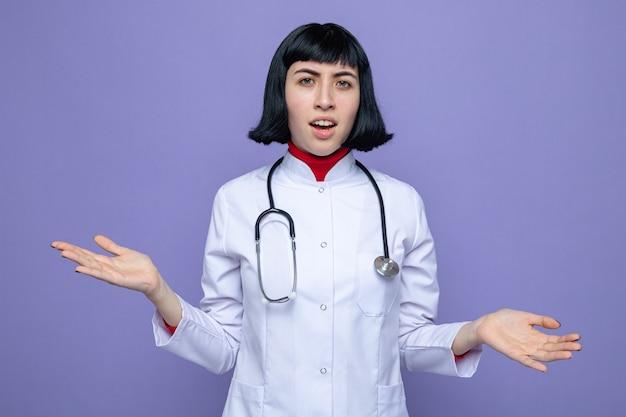 Jeune jolie fille caucasienne ignorante en uniforme de médecin avec stéthoscope gardant les mains ouvertes