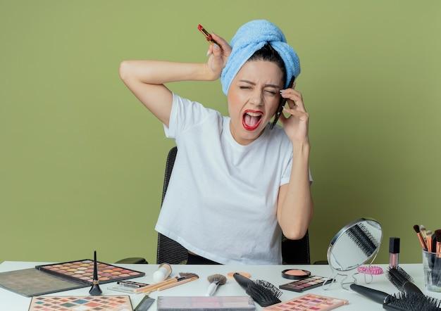 Jeune jolie fille en colère assise à la table de maquillage avec des outils de maquillage et avec une serviette sur la tête parlant au téléphone touchant la tête avec du rouge à lèvres à la main criant les yeux fermés sur un espace vert olive
