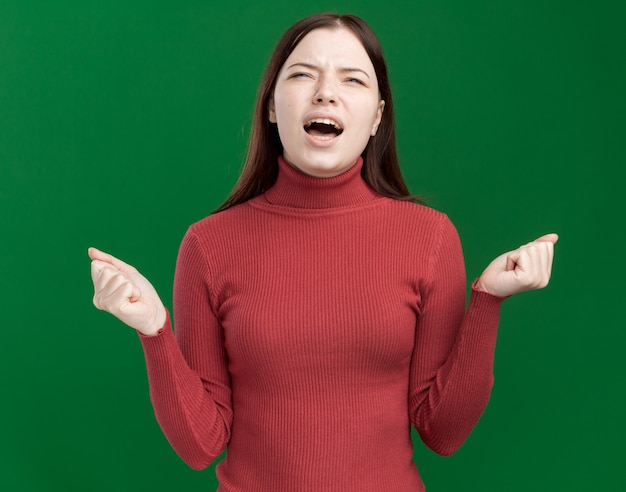 Jeune jolie fille en colère jusqu'à crier avec les poings fermés