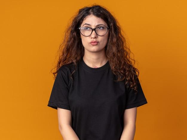 Jeune jolie fille confuse portant des lunettes regardant de côté