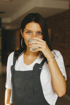 Jeune jolie fille dans des vêtements décontractés, boire du café au café