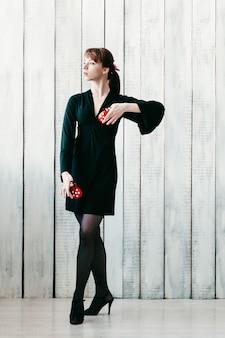 Jeune jolie fille dansante en robe noire, avec des castagnettes rouges