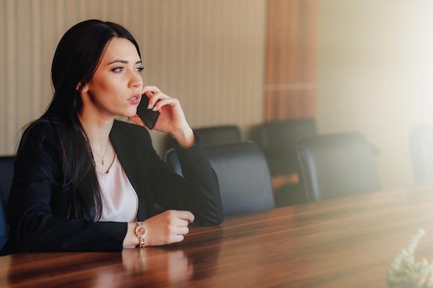Jeune jolie fille émotionnelle en vêtements de style professionnel assis au bureau avec téléphone au bureau ou au public