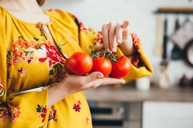 Jeune jolie fille enceinte préparant une salade de légumes dans la cuisine